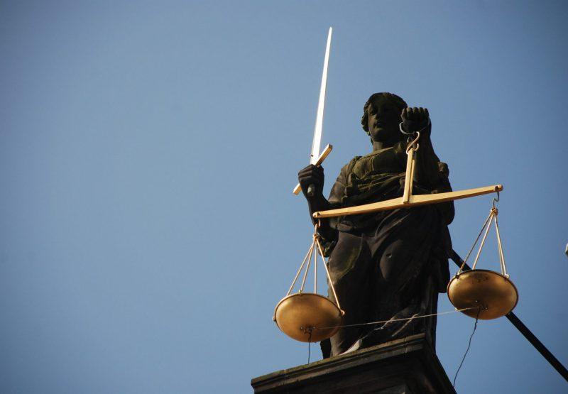 Thémis, l'épée et la balance de la justice à la main. Vu d'en bas, sur un ciel bleu. Pixabay, Edward Lich/AJEL