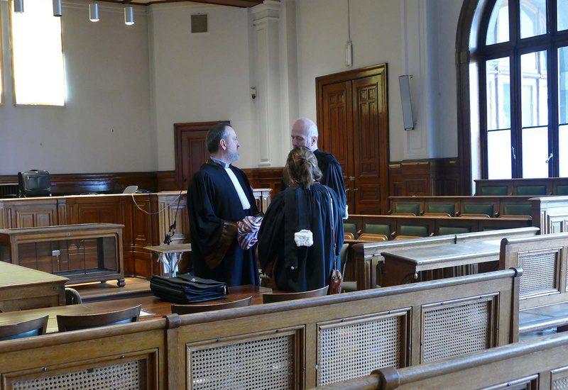 Trois avocats qui discutent dans un tribunal du Palais de justice de première instance de Namur. Ils discutent après une audience de cours d'assise.
