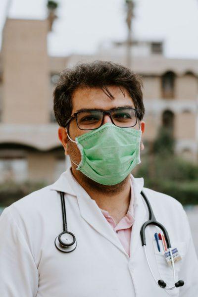 personne en blouse blanche portant un masque chirurgical