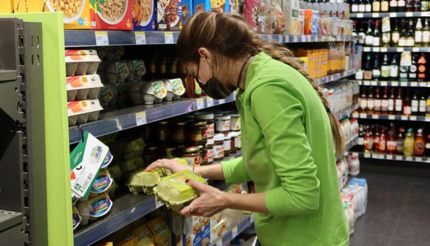 Etudiante met des boîtes d'œufs sur un rayon de supermarché